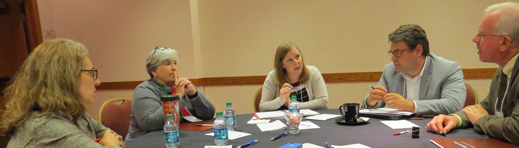 4 summit participants listen attentively to another participant during small group discussion