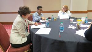 Summit participants share best practices and take notes during small group discussion